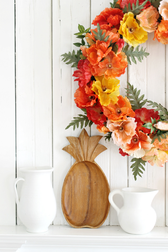 Orange, peach, and yellow poppy flower wreath on wall as spring home décor