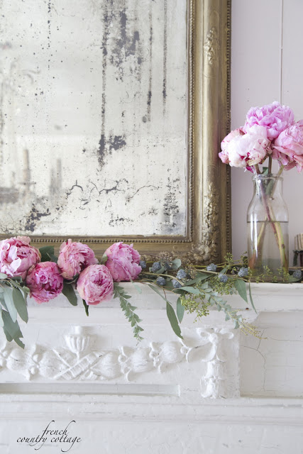 Pink peonies and mirror with gold frame as mantel decor