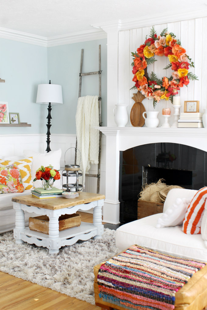 Orange, peach, and yellow poppy flower wreath in living room as easter fireplace mantel decorations