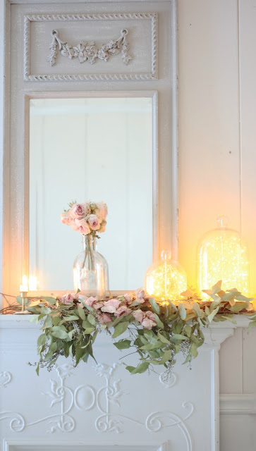 Roses and fairy string lights in glass cloches as spring mantel ideas