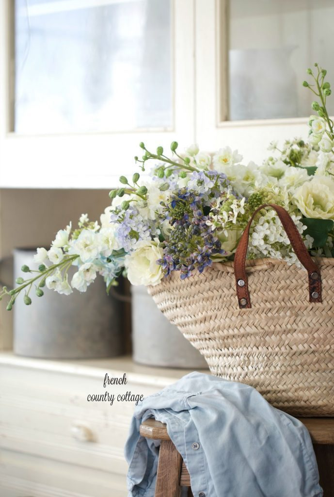 Spring mantel floral arrangements in a wicker tote bag