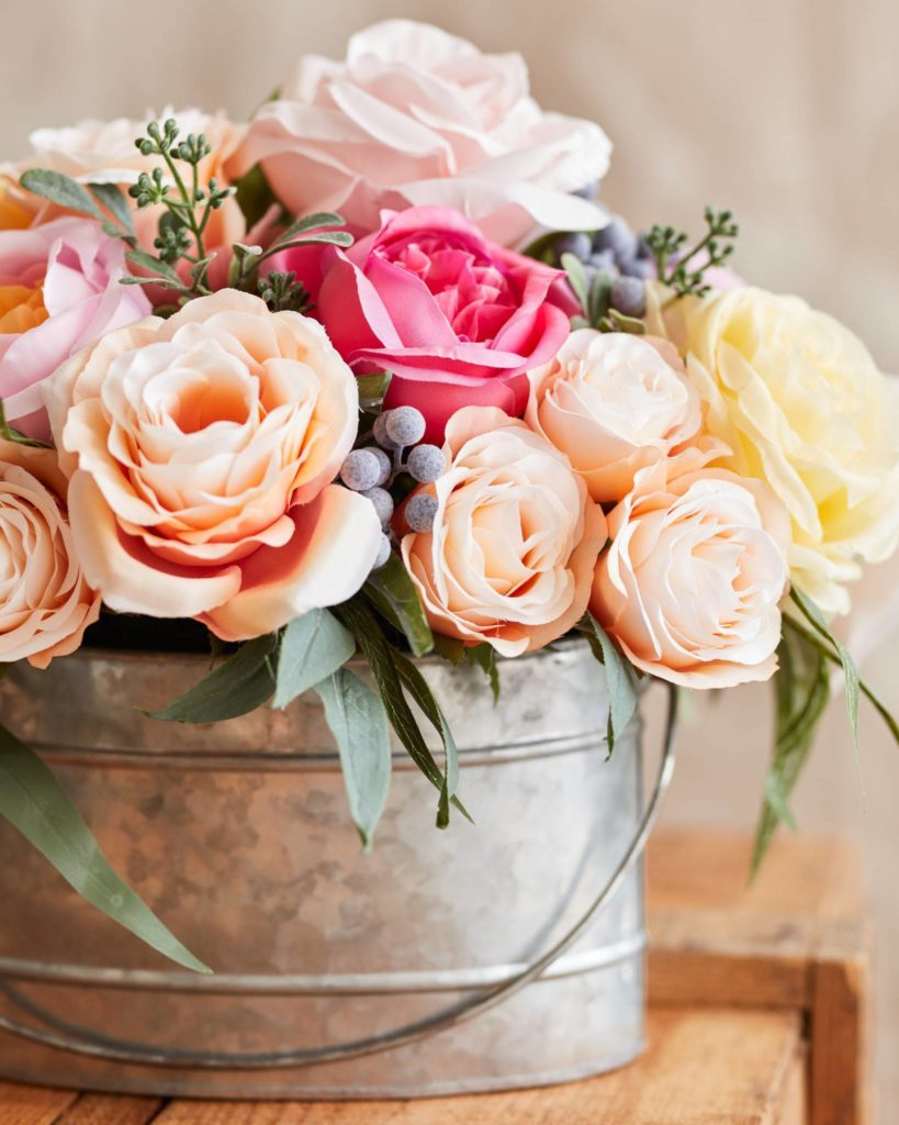 Pink, peach, yellow, and white roses in tin bucket as mantel floral arrangements