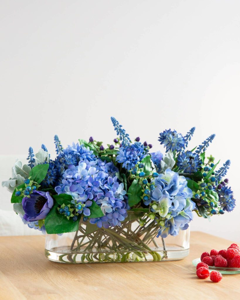 Blue cornflower, anemones, hydrangeas, hypericum berries, and muscari in glass vase as mantel floral arrangements