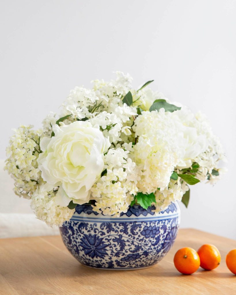 Peonies, lilacs, snowballs, and apple blossom picks mantel floral arrangements in blue and white Chinoiserie ceramic vase