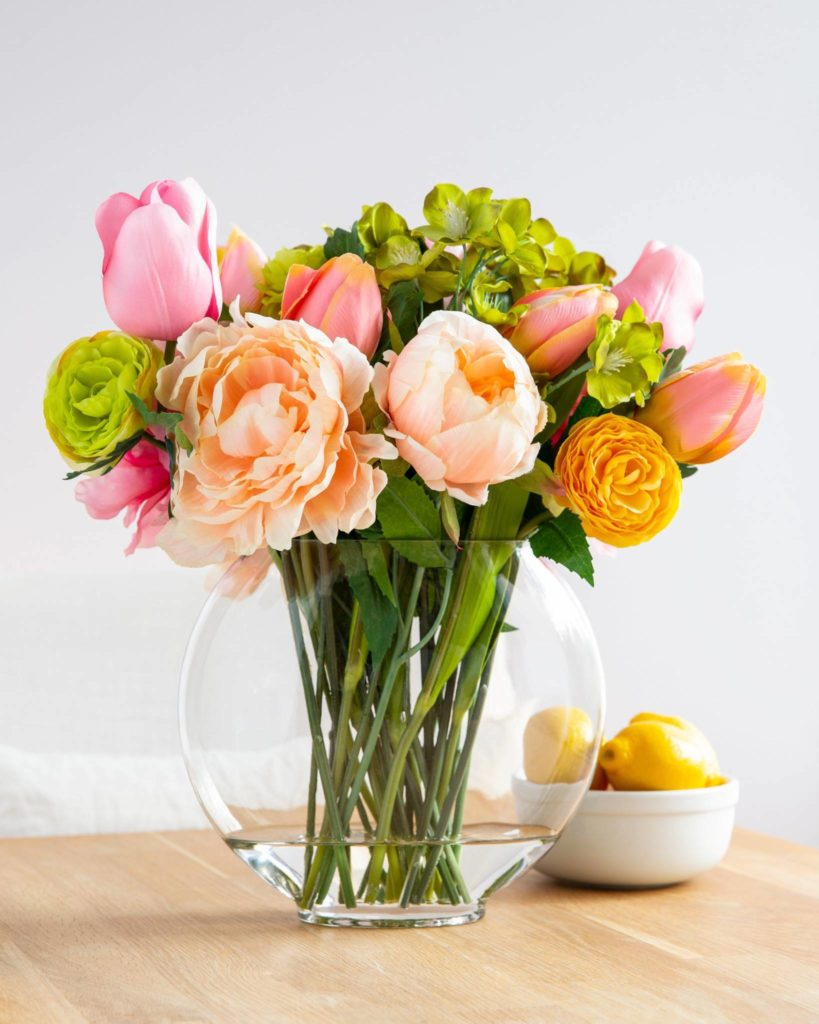 Peonies, ranunculus, tulips, and hellebore in glass vase as fireplace mantel flower arrangements