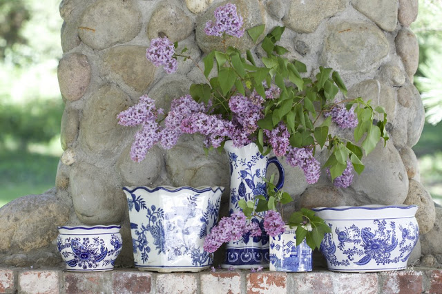 Blue and white Chinoiserie ceramic containers with lilacs as outdoor fireplace mantel décor