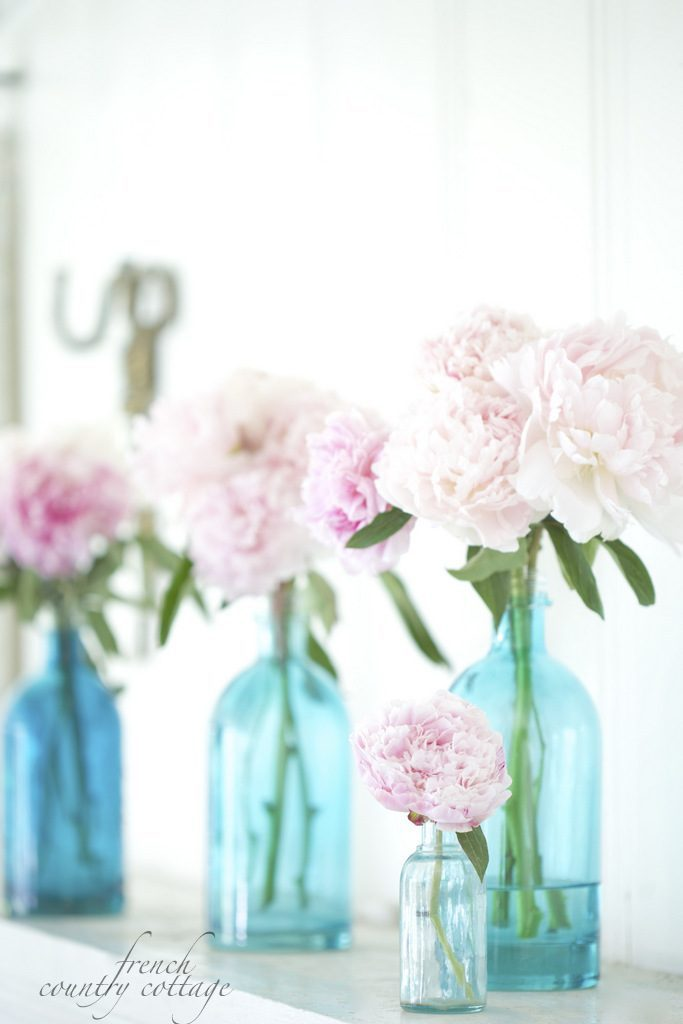 Big blue seltzer bottles and small clear bottle with pink peonies as spring decorating ideas for mantels