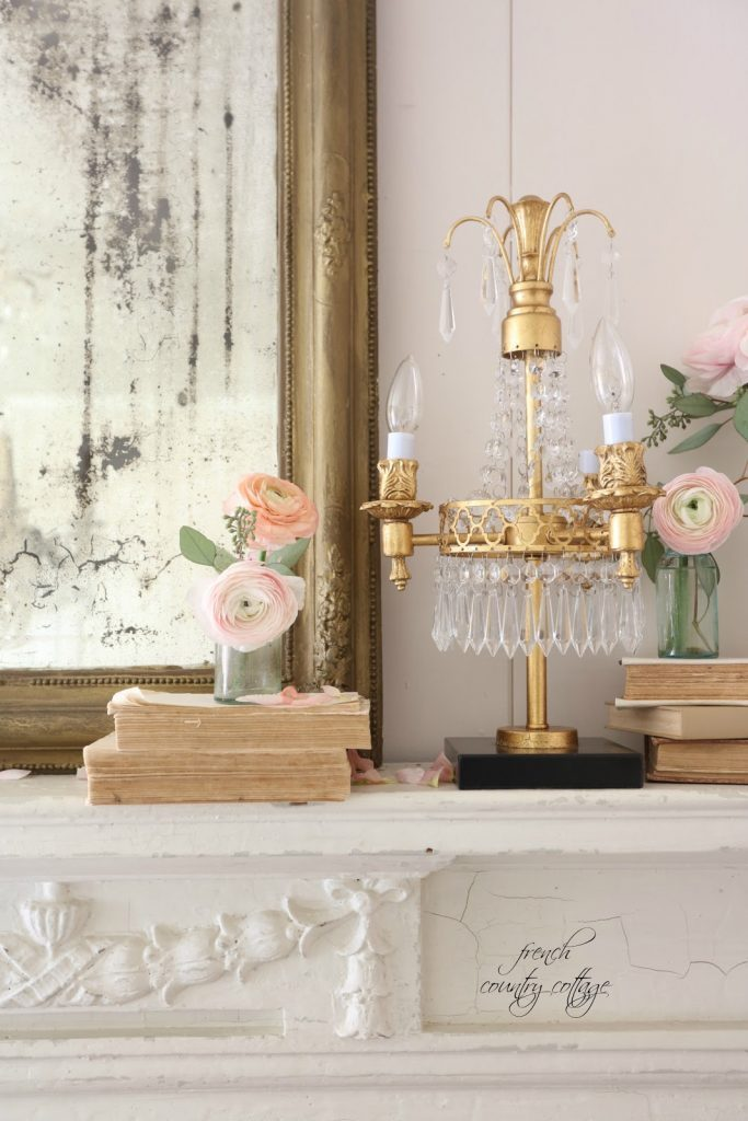 Pink Italian ranunculus in glass bottles, a gold lamp, a mirror with a gold frame, and books as spring mantel décor ideas