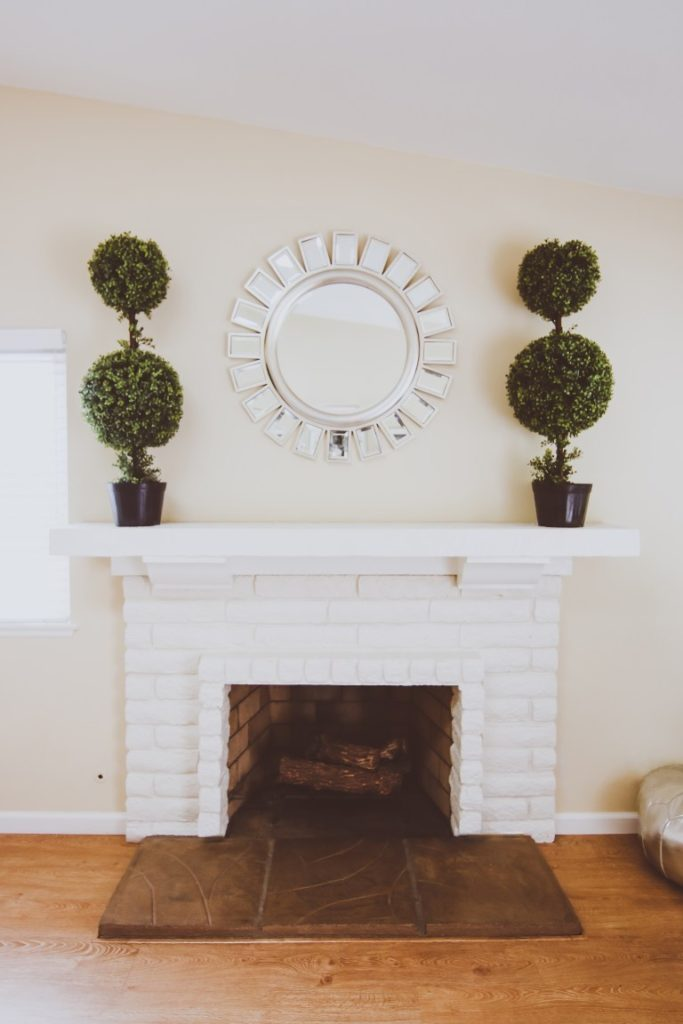 Two boxwood topiaries framing a round mirror in the center of a spring mantel
