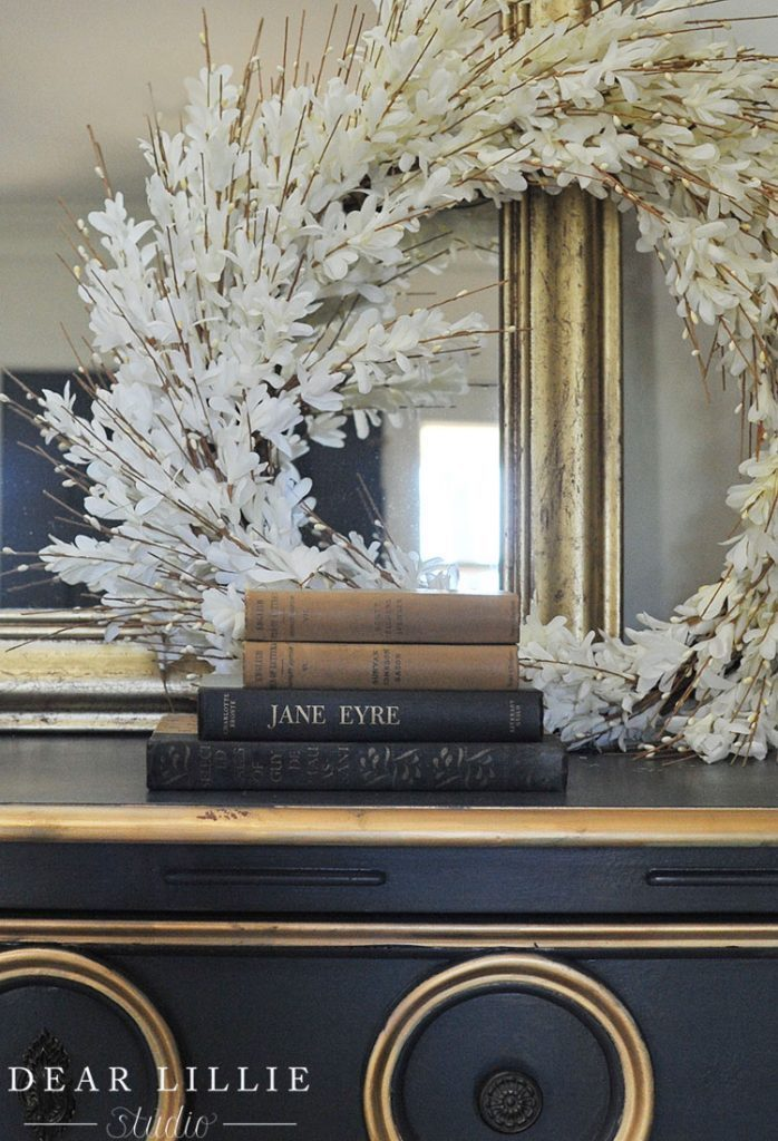 White Forsythia wreath, books, and mirror with gold frame as spring mantel décor ideas