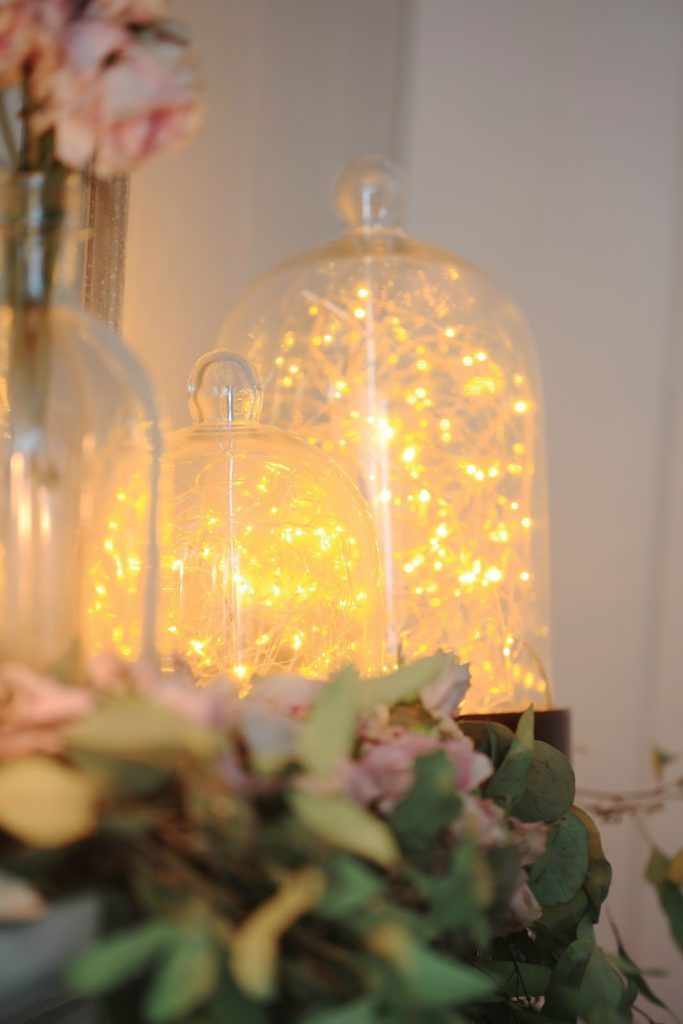 Fairy string lights in glass cloches as spring mantel décor ideas