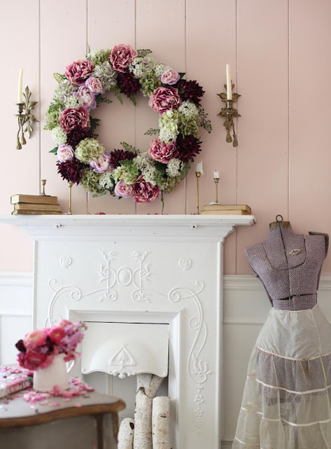 Blush pink wall with Peony flower wreath, candles, and books as spring mantel ideas