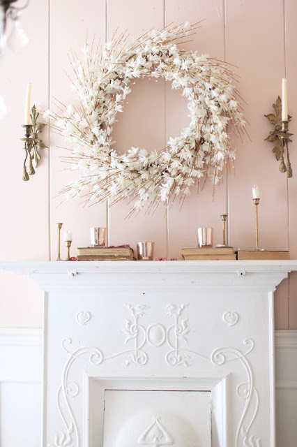 White Forsythia Wreath on pink wall with candles, rose gold glasses, and books as easter fireplace decorations