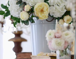 Mantel flower arrangements in tin bucket and jar with books