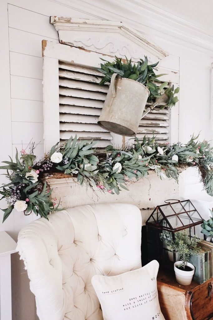 Ranunculus and waxflower garland with leaves on tin watering can over distressed wood shutters as fireplace mantel décor