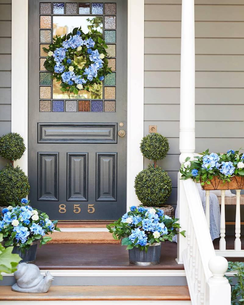 artificial foliage with blue hydrangeas on front porch