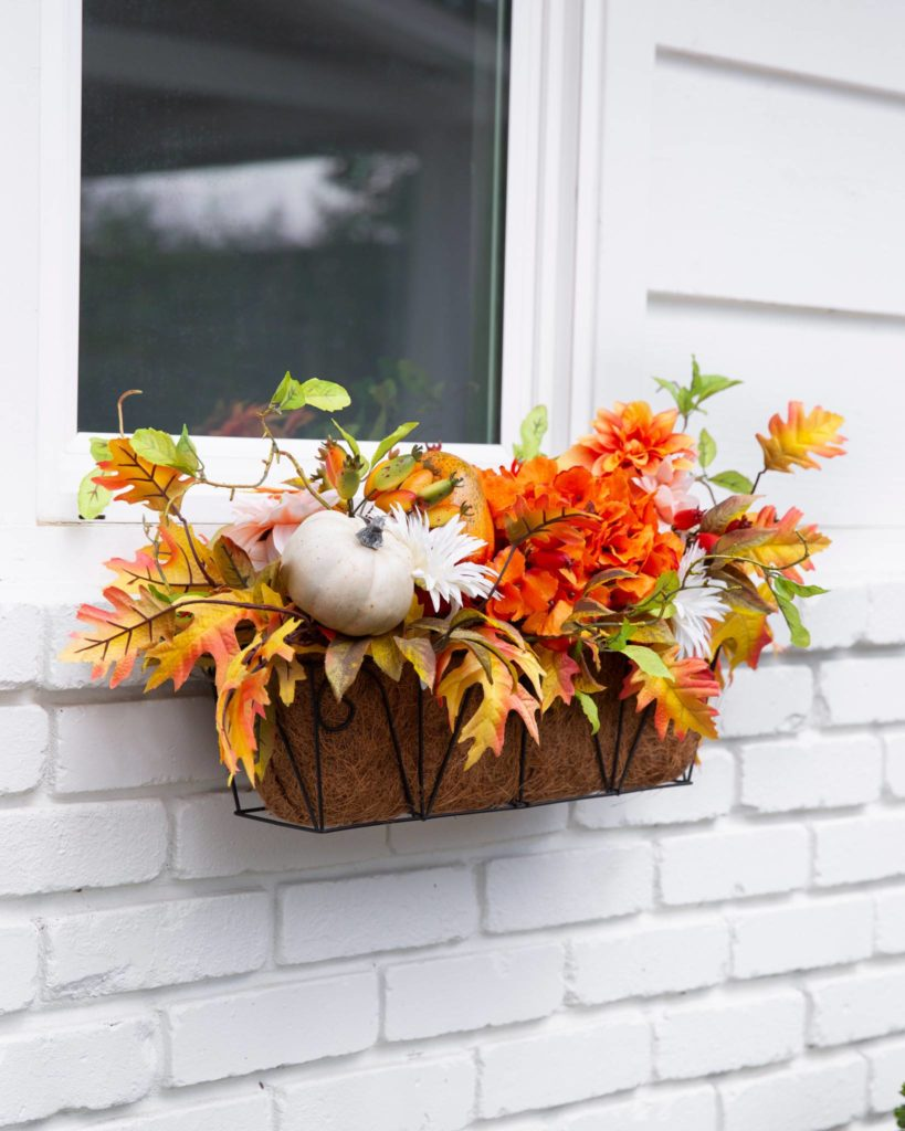 fall-themed window basket with flowers and pumpkins