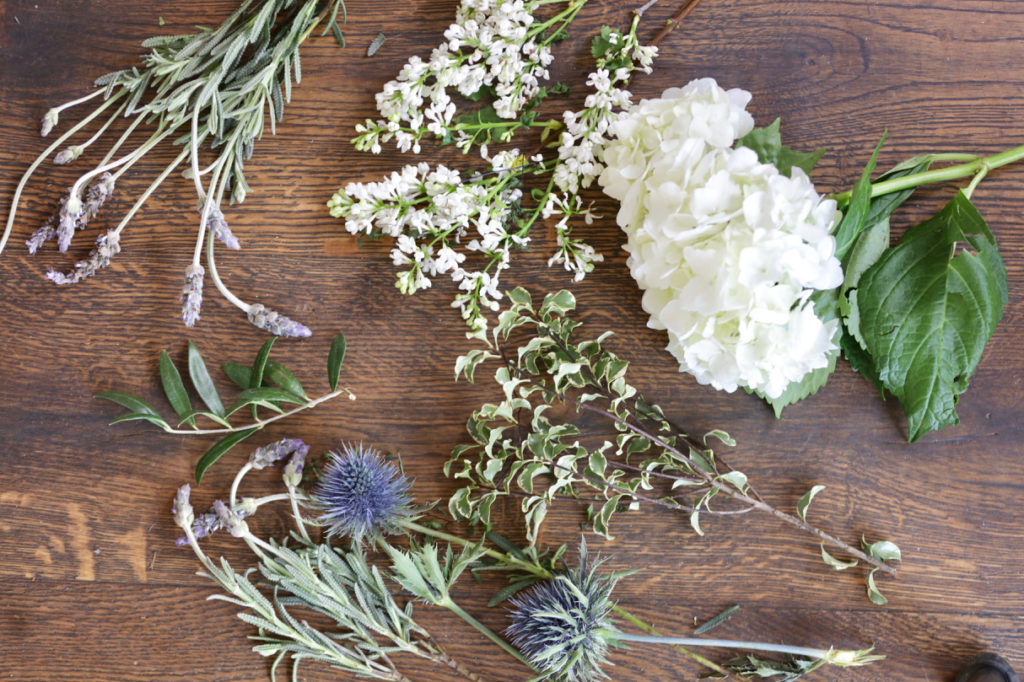 Fresh thistle, lavender, white lilac, white hydrangea, olive branches, yellow berries, and pittosporum