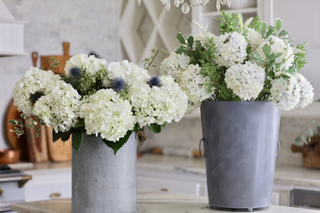 Balsam Hill Nantucket Hydrangea Foliage in metal vessel beside its replica made with fresh flowers