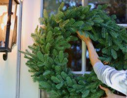 woman hanging an artificial wreath on a door