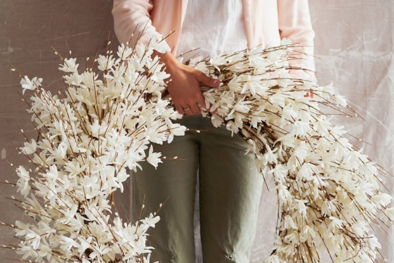 woman holding a large white floral wreath