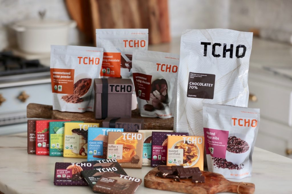 Assorted Tcho Chocolate Products such as flavored chocolate bars, baking chocolate, cocoa powder, dark chocolate discs, and cacao nibs