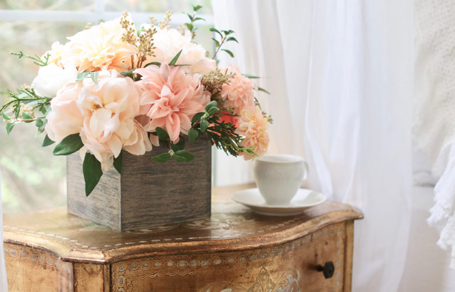 Realistic faux florals on the nightstand in a bedroom as room décor