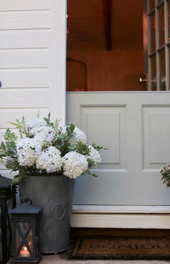 Faux hydrangeas in bucket beside the door
