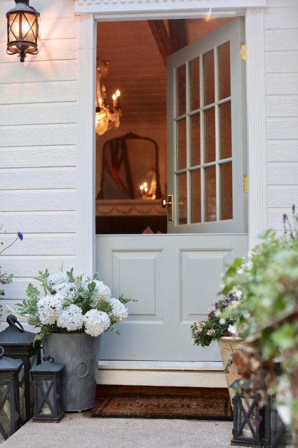 Faux flowers in bucket beside a door
