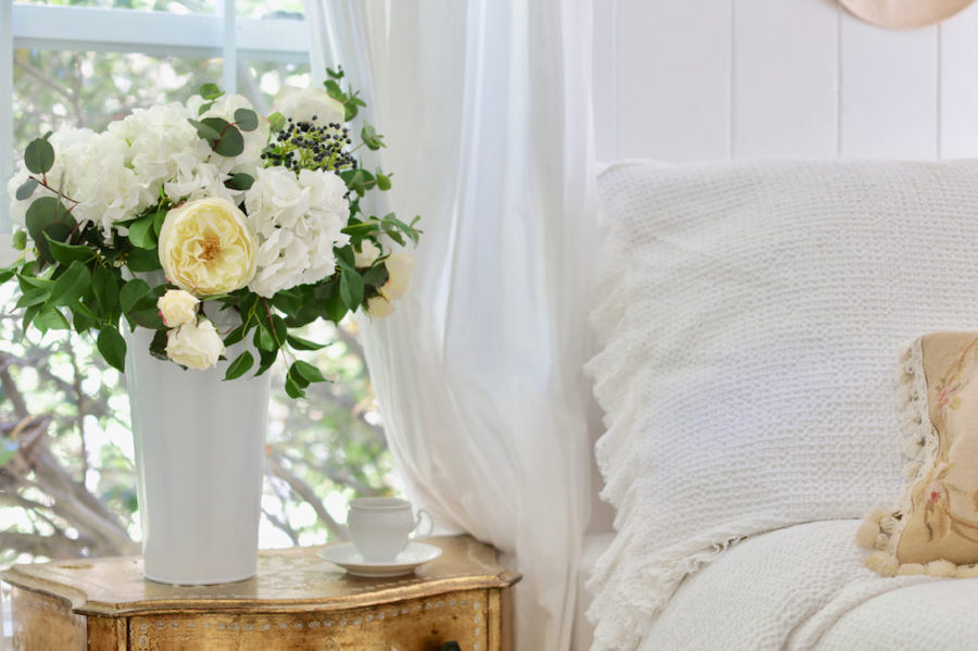 Tall floral arrangement as room décor in guest bedroom