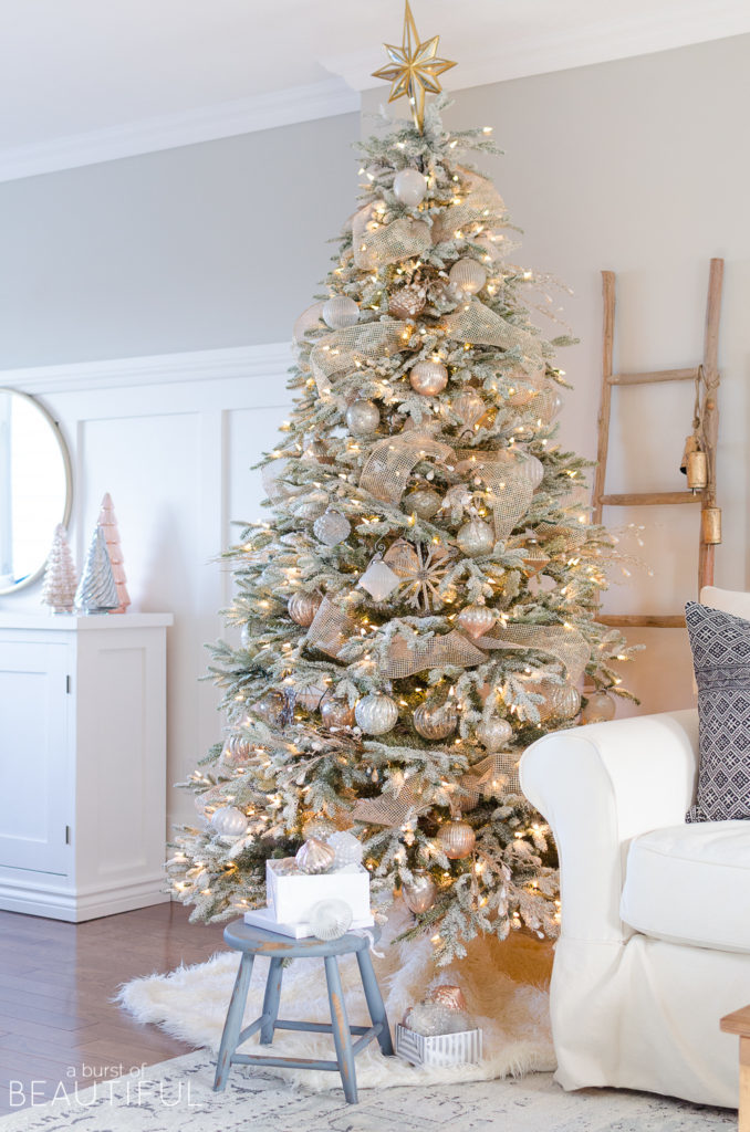 A lit-up Christmas tree with frosted branches and assorted ornaments.
