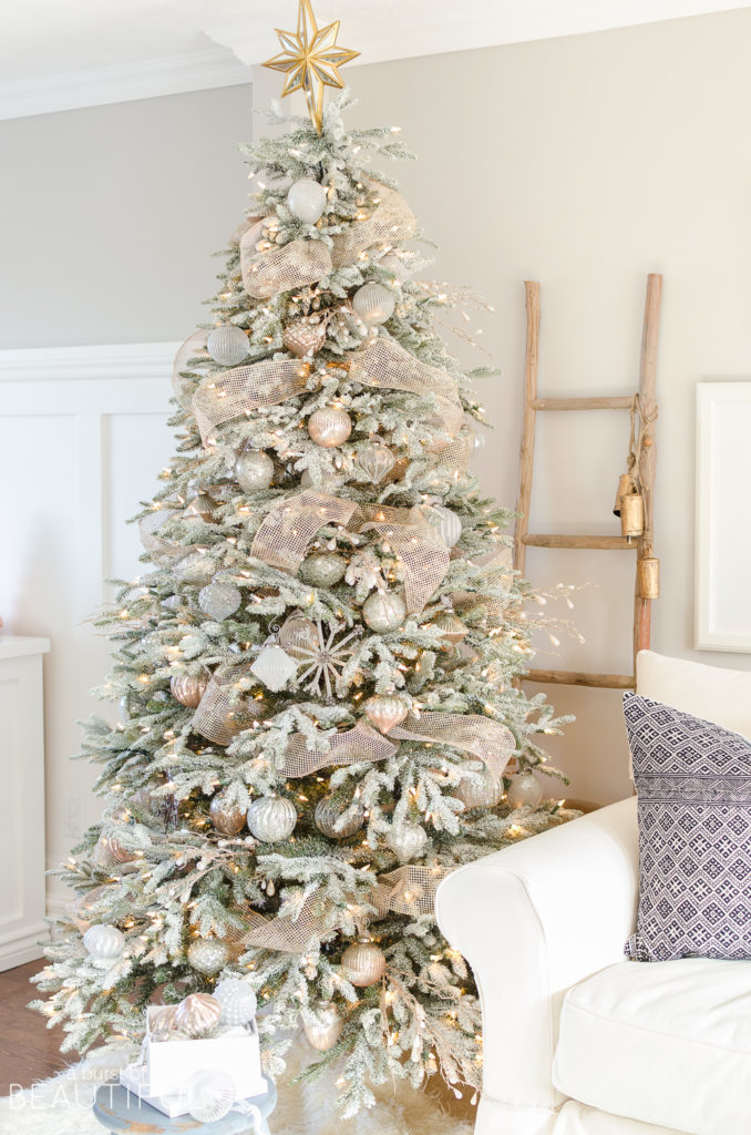 A lit-up Christmas tree with frosted branches, gold ribbons, and assorted white, gold, and silver ornaments.