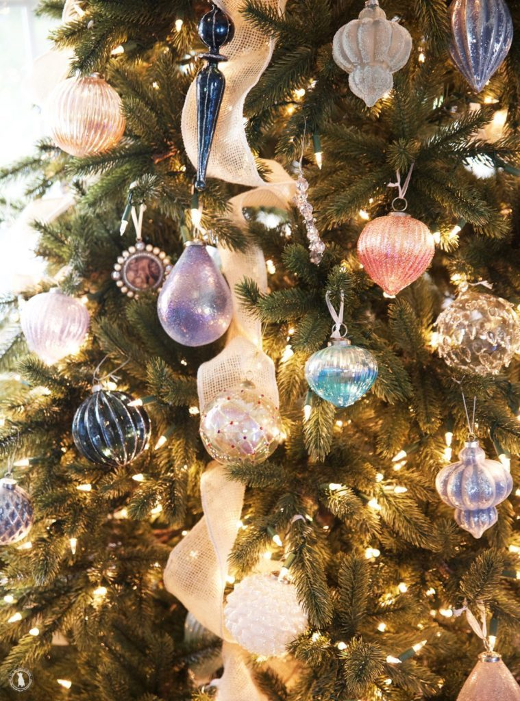 Closeup shot of pastel and cool-toned ornaments hanging from a lit-up Christmas tree