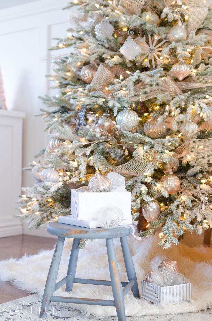 A box of ornaments placed on a stool by the foot of a lit-up Christmas tree
