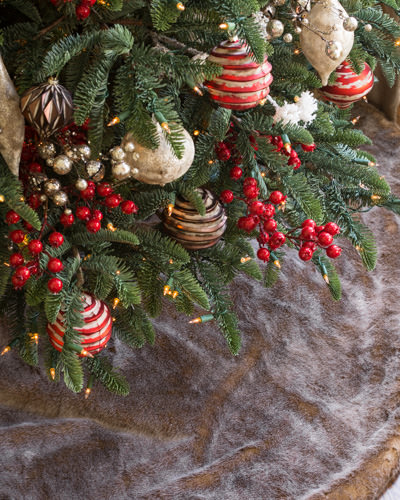 Closeup shot of the bottom branches of a Christmas tree decorated with assorted ornaments and berry picks