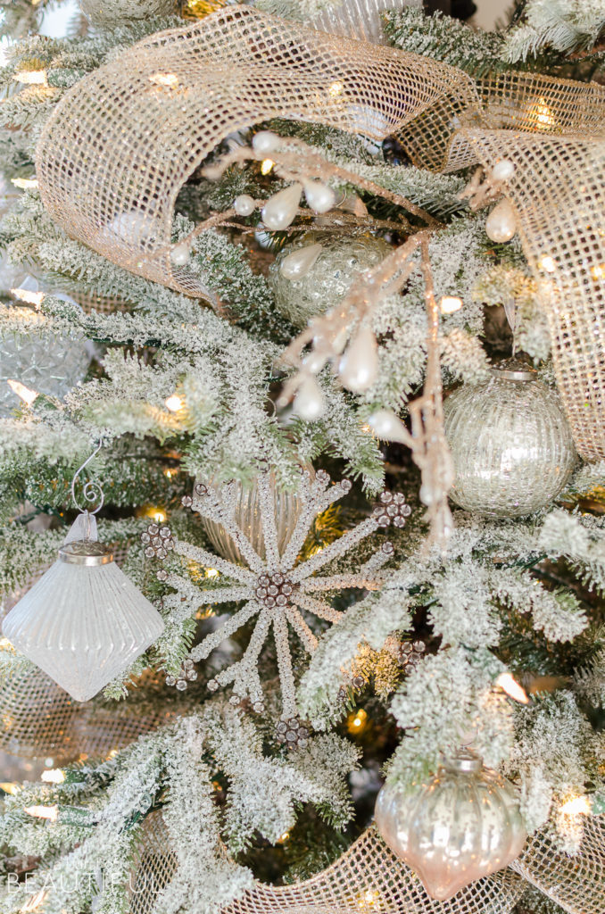 Closeup shot of a lit-up Christmas tree with frosted branches, white and gold ornaments, and a gold net ribbon.