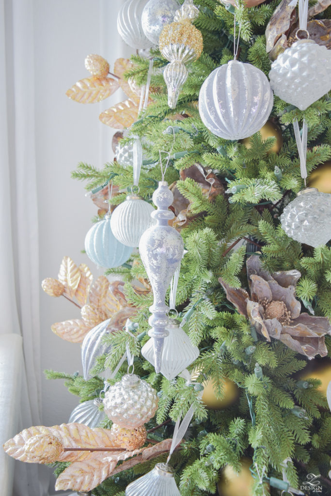 Closeup shot of silver and gold ornaments hanging from a Christmas tree