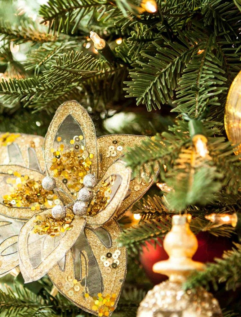 Closeup shot of a gold sequined flower accent placed on a Christmas tree