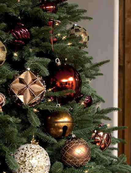 Closeup shot of a lit-up Christmas tree decorated with assorted metallic ornaments
