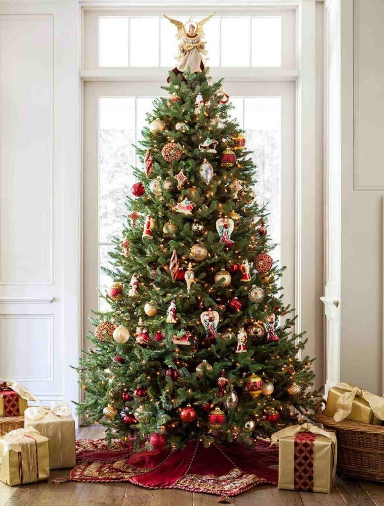 A lit-up Christmas tree decorated with assorted ornaments and an angel tree topper