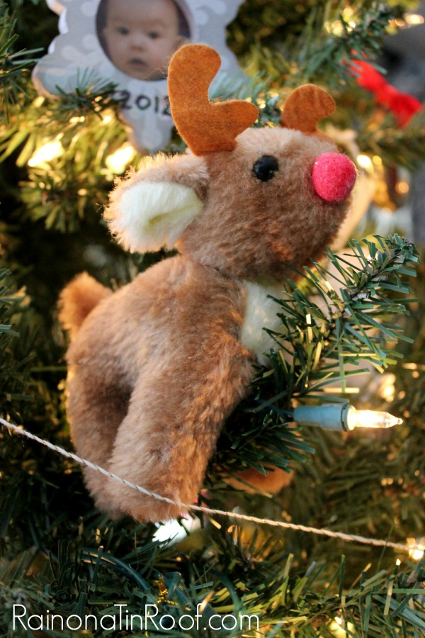 Closeup shot of a reindeer ornament hanging from a Christmas tree