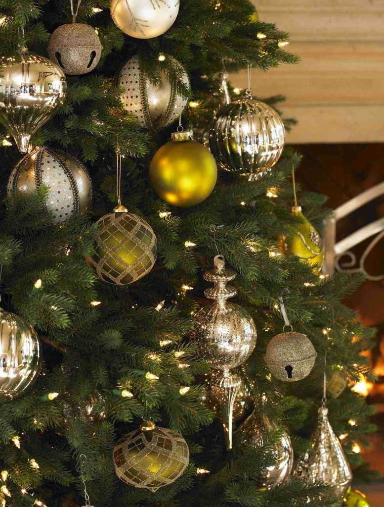 Closeup shot of a lit-up Christmas tree decorated with assorted ornaments