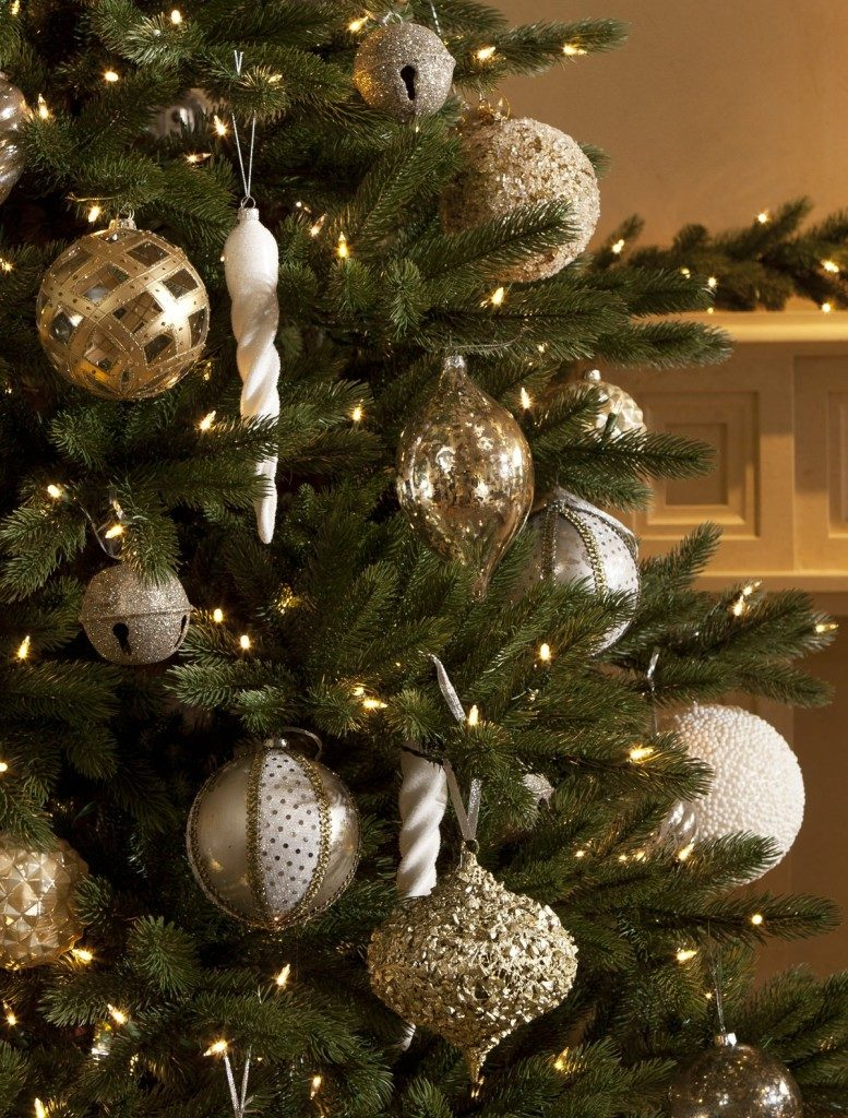 Closeup shot of assorted silver and gold ornaments hanging from a lit-up Christmas tree.