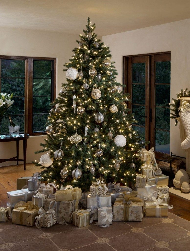 A lit-up Christmas tree decorated with assorted silver and gold ornaments and presents underneath