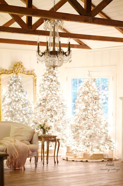 pre-lit frosted fir trees in the living room