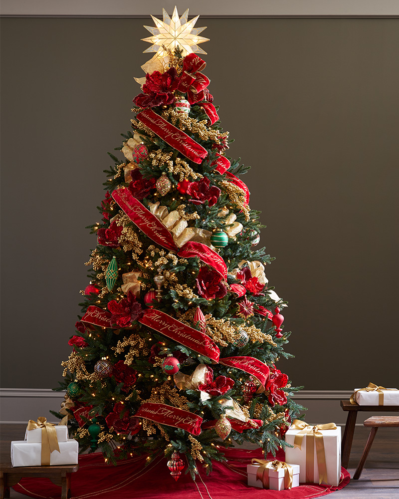 A Christmas tree decorated with red, gold, and green accents and ribbons