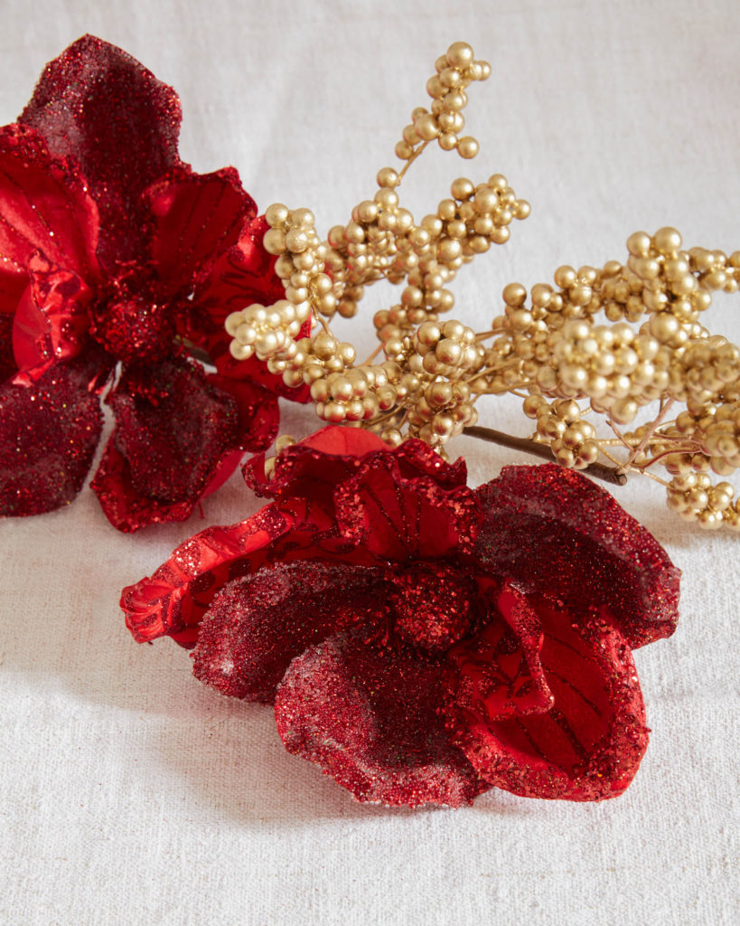 Closeup shot of tree picks with red artificial flowers and gold berries