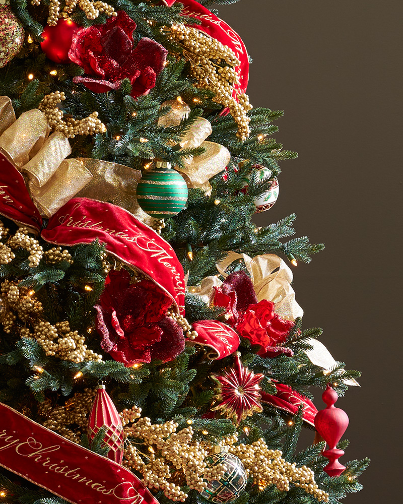 Closeup shot of a Christmas tree decorated with red, gold, and green accents and ribbons