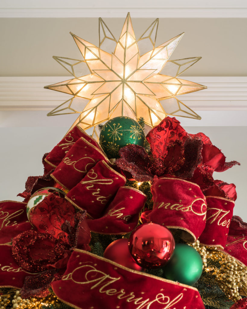Closeup shot of a lighted star tree topper and red ribbons placed on top of a Christmas tree
