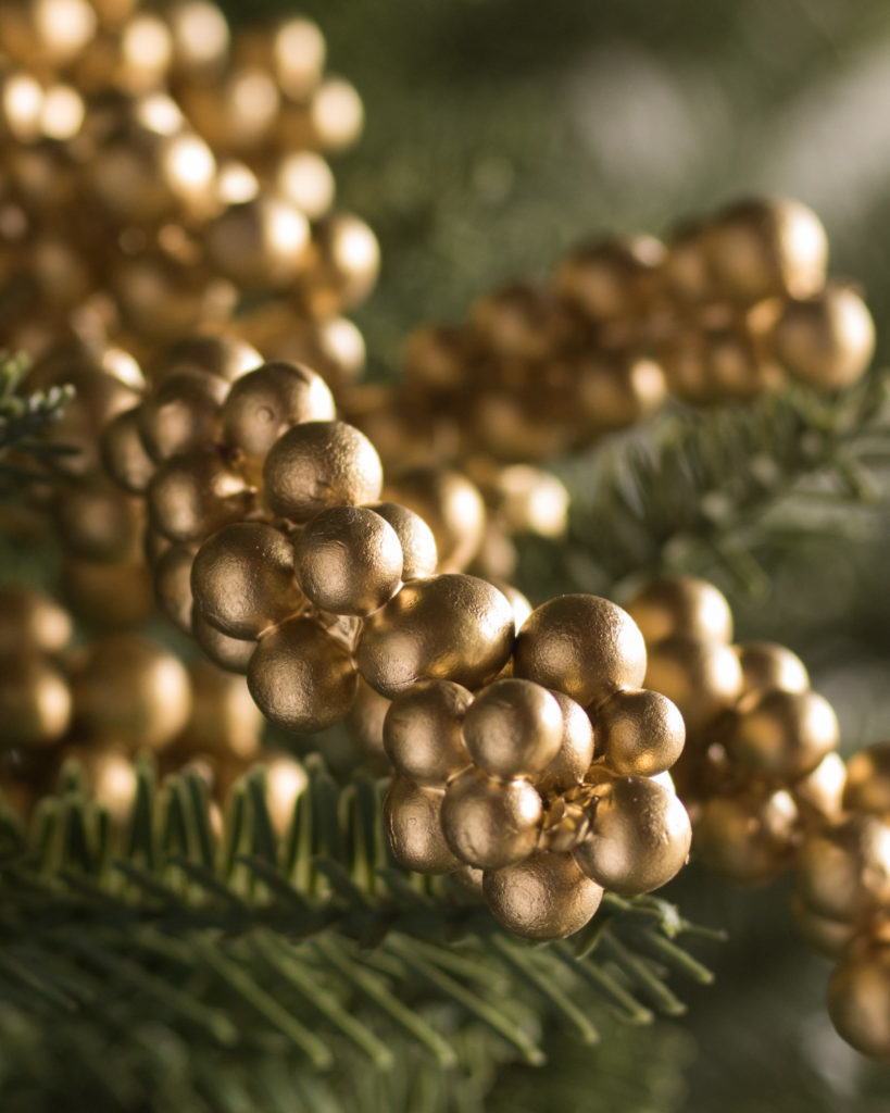 Closeup shot of a gold berry tree pick attached to a Christmas tree